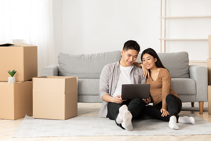 Couple sitting on floor of new home while smiling at their laptop